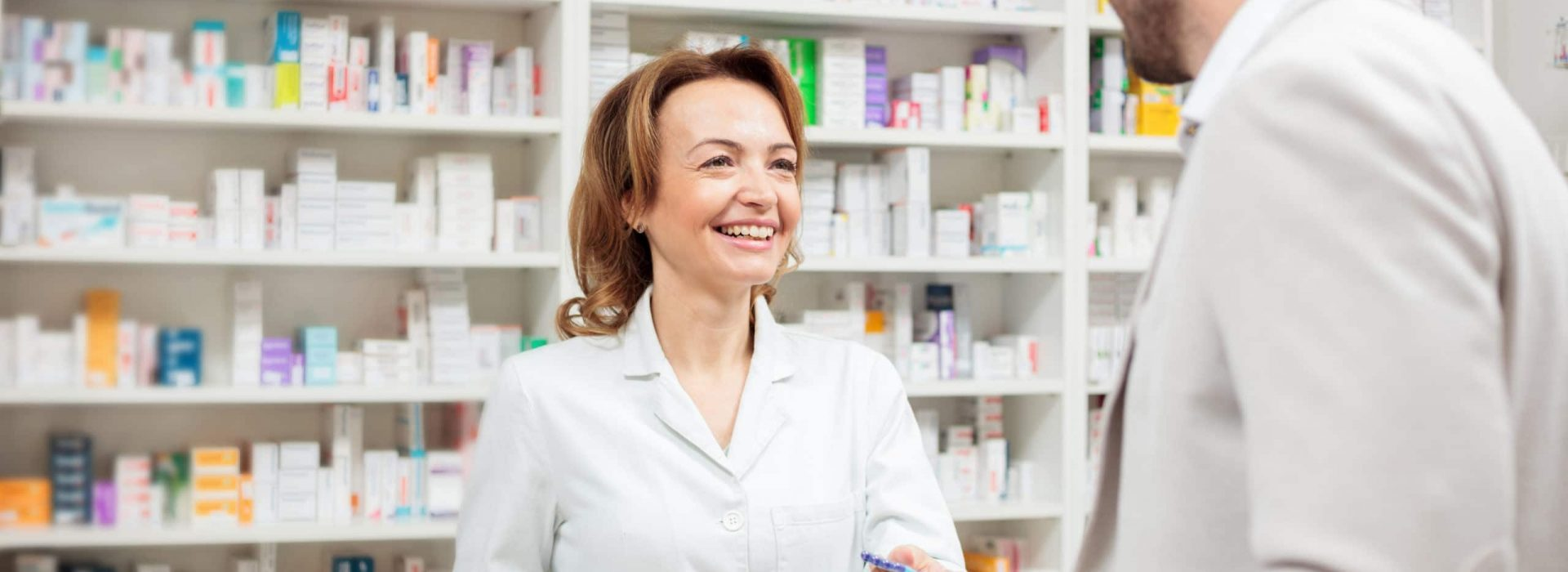 Smiling, happy female pharmacist serving young male customer, giving advice and helping to make right decision. Healthcare and medicine concept